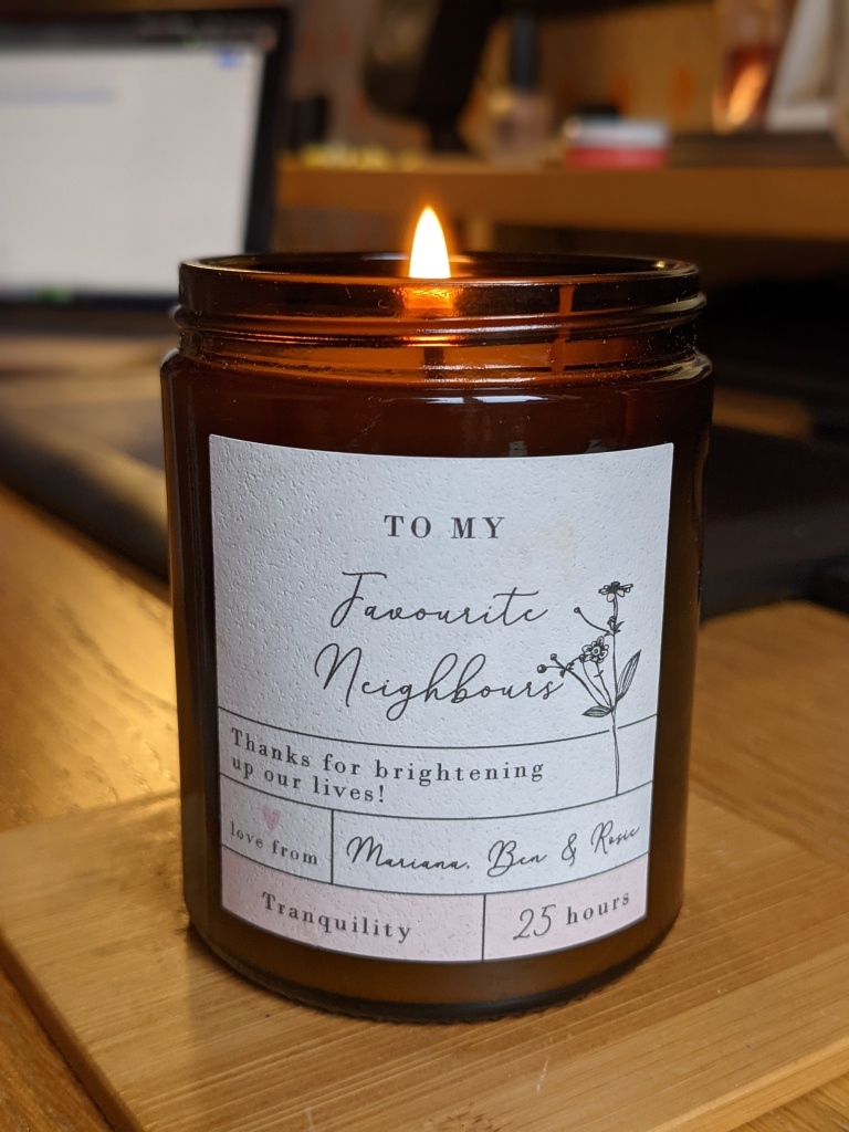 """A candle on a desk with a label saying """"Favourite Neighbors"""""""